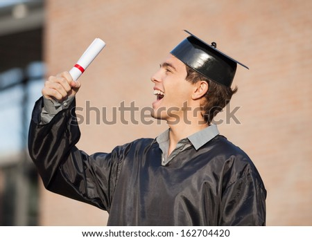 Excited male student holding diploma on graduation day in college - stock photo