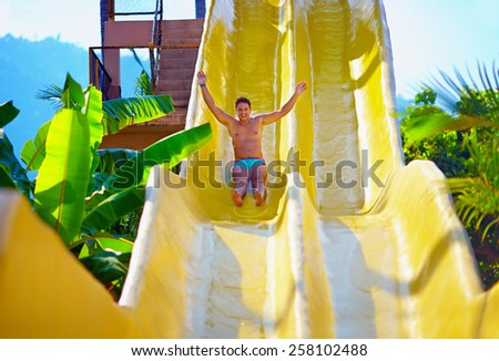 excited man having fun on water slide in tropical aqua park - stock photo