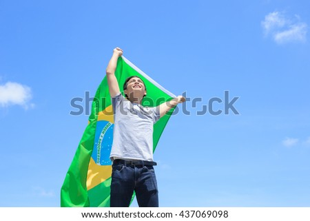 Excited man holding a brazil flag with blue sky
