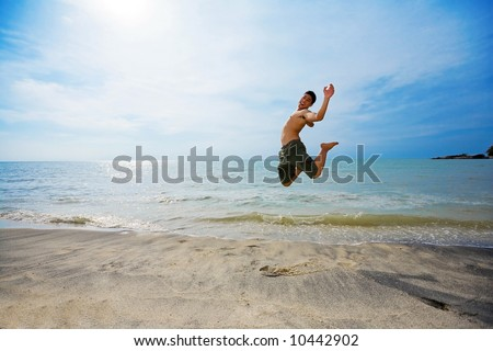excited man jump up high happily by the beach