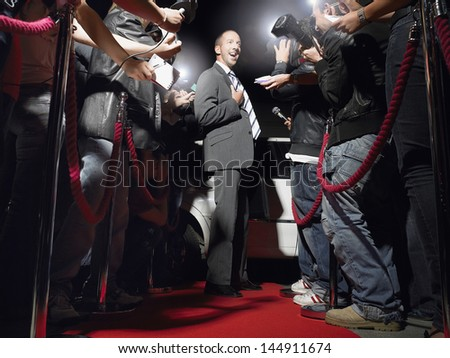 Excited man on red carpet by limousine posing in front of paparazzi