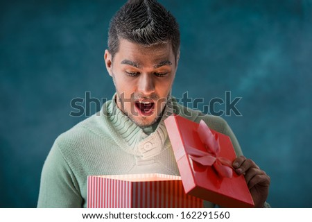 Excited man opening big gift box outdoors at winter. Frost on his face - stock photo