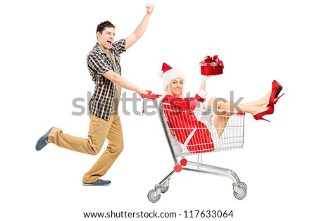 Excited man pushing a shopping cart and woman in christmas costume isolated on white background - stock photo
