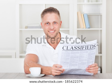 Excited man reading the classifieds cheering as he comes across good news  a bargain or a suitable employment opportunity