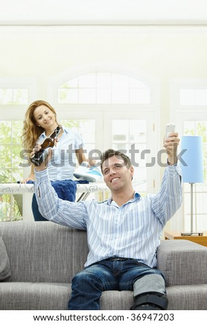 Excited man sitting at couch watching TV, woman ironing in the background. Selective focus on man. - stock photo