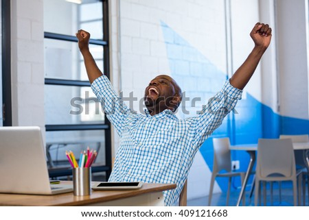 Excited man sitting on table with digital tablet and laptop in office - stock photo