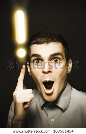 Excited man with an idea gestures up to an explanation mark in a depiction of finding the answer to questions - stock photo