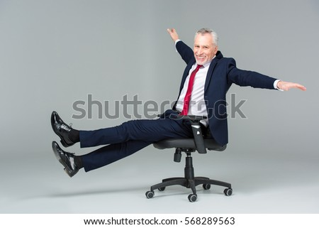 Excited mature businessman in office chair isolated on grey