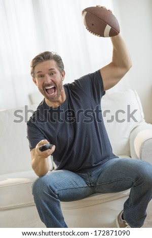 Excited mature man cheering while watching American football match on sofa - stock photo