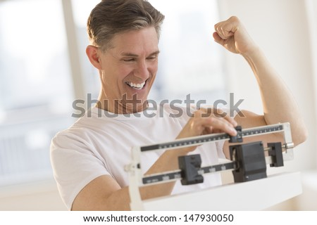 Excited mature man clenching fist while using balance weight scale at gym - stock photo