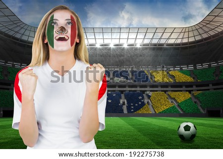 Excited mexico fan in face paint cheering against large football stadium with brasilian fans - stock photo