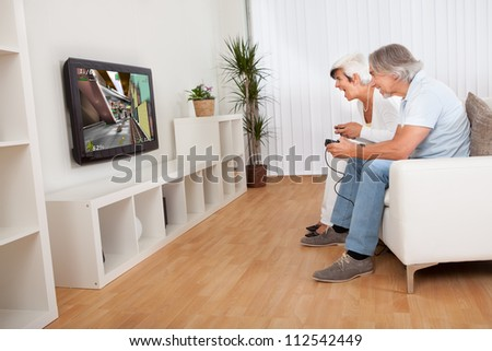 Excited middle-aged couple sitting on a sofa in their living room in front of the television screen playing computer games