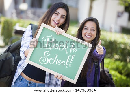 Excited Mixed Race Female Students Holding Chalkboard With Back To School Written on it. - stock photo