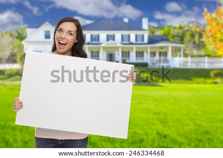Excited Mixed Race Female with Blank Sign In Front of Beautiful House. - stock photo