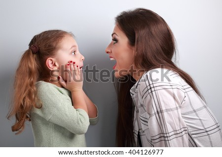 Excited mother and surprising kid girl looking on each other with opened mouth on blue background