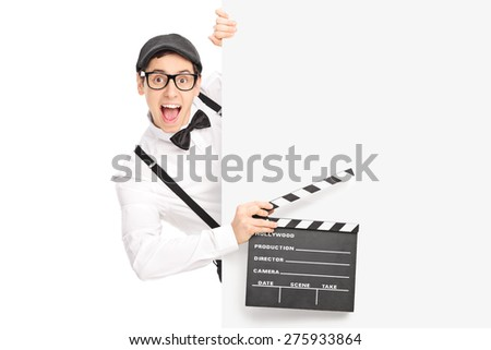 Excited movie director holding a movie clapperboard and posing behind a blank panel isolated on white background - stock photo