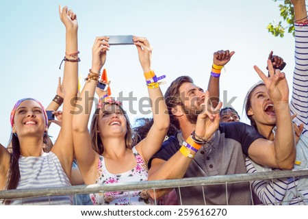 Excited music fans up the front at a music festival - stock photo