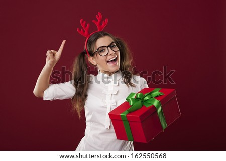 Excited nerdy woman with red christmas present - stock photo