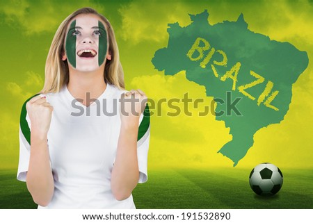 Excited nigeria fan in face paint cheering against football pitch with brazil outline and text - stock photo