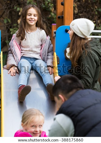 Excited parents with two daughters playing at children's slide - stock photo