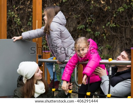 Excited parents with two little daughters playing at children's slide