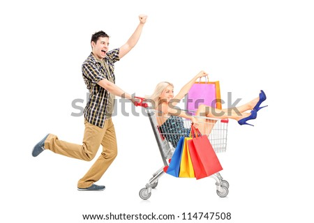 Excited person pushing a smiling woman with bags in a shopping cart isolated on white background - stock photo
