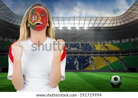 Excited portugal fan in face paint cheering against large football stadium with brasilian fans - stock photo