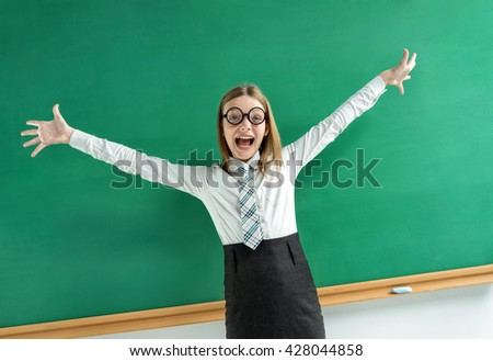 Excited pupil happy smile with her raised hands arms palms. Photo of teen school girl wearing glasses, creative concept with Back to school theme - stock photo