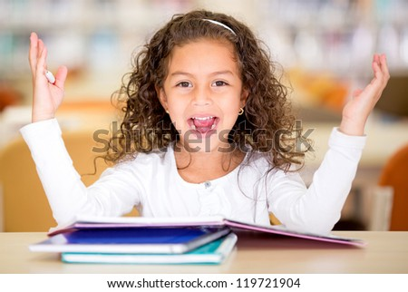 Excited school girl at the library looking surprised - stock photo