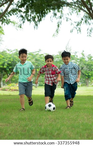 Excited schoolboys playing soccer in the park - stock photo