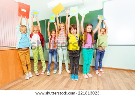 Excited schoolchildren hold textbooks up with arms