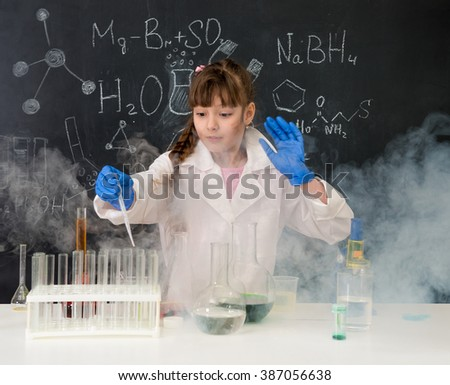 excited schoolgirl in fume after chemical experiment in school lab - stock photo