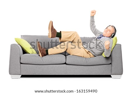 Excited senior male seated on a sofa listening music isolated on white background - stock photo