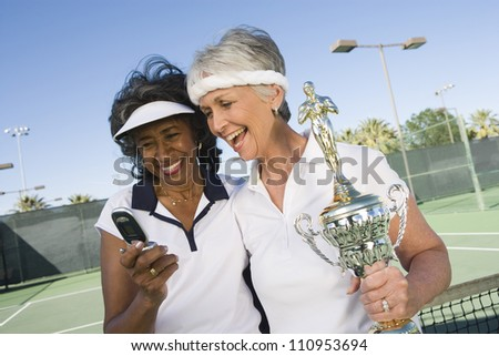 Excited senior tennis players with trophy checking self portrait - stock photo