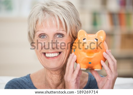 Excited senior woman holding up her piggy bank smiling in anticipation of a planned vacation or purchase to be paid for from her nest egg and savings - stock photo