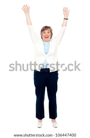 Excited senior woman posing with raised arms. Enjoying herself - stock photo
