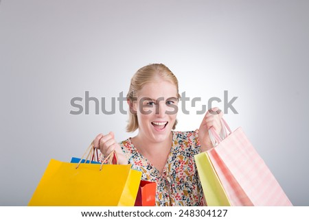 Excited shopaholic holding many paper bags