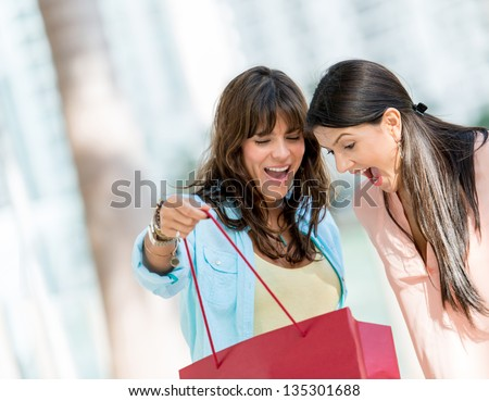 Excited shopping women looking in a bag - stock photo