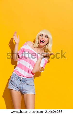 Excited smiling blonde spread her hands. Laughing blonde spread her hands and looking up. Three quarter length studio shot on yellow background. - stock photo