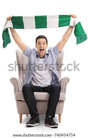 Excited sports fan sitting in an armchair and holding a scarf isolated on white background