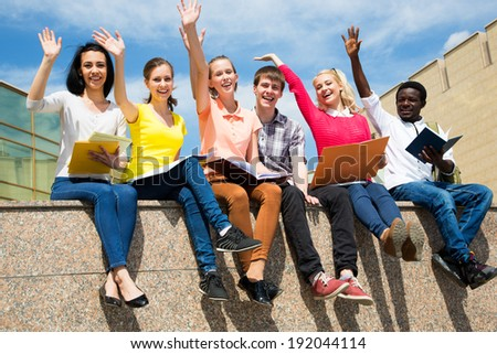 Excited students with arms outstretched outdoors - stock photo