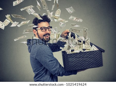 Excited successful business man opening a box with money flying out away