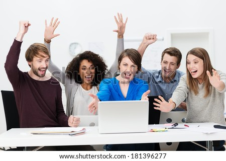 Excited successful business team of diverse multiethnic young people sitting at a table in the office cheering exuberantly as they celebrate a successful outcome on the laptop computer