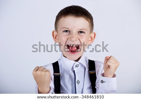Excited Surprised  little boy holding his fist up with  isolated over white background. - stock photo