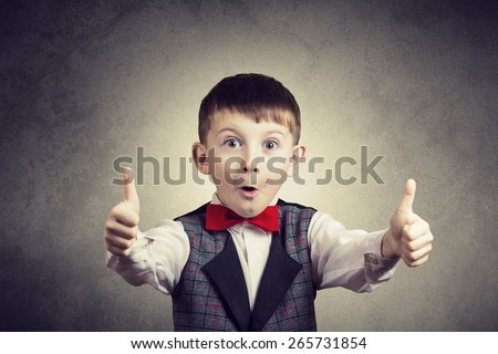 Excited Surprised  little boy with thumb up gesture isolated over grey background. - stock photo