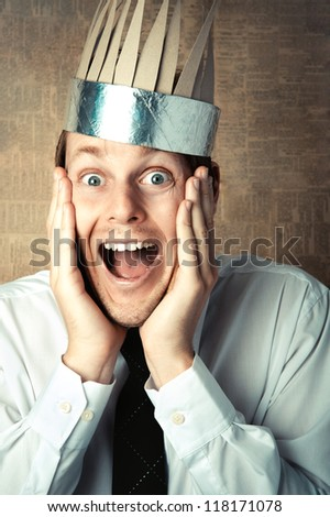 Excited surprised man with wide open mouth and a crown on his head - stock photo