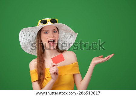Excited surprised summer woman in yellow summer dress and a straw hat, showing blank credit card  and open hand palm with copy space for product or text, on green background