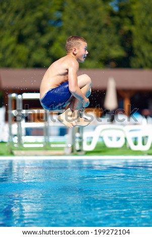 """excited teenage boy jumping """"bomb"""" in the pool - stock photo"""