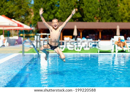 excited teenage boy jumping in the pool - stock photo