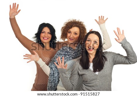 Excited three women friends with hands in the air isolated on white background